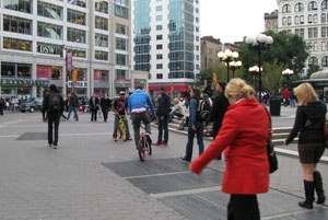 Pedestrians and bicyclists travel across a crowded plaza in New York City.