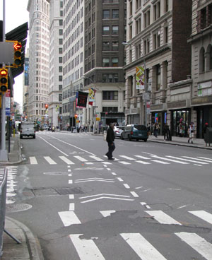 A pedestrian crosses a city street in a crosswalk in New York City.