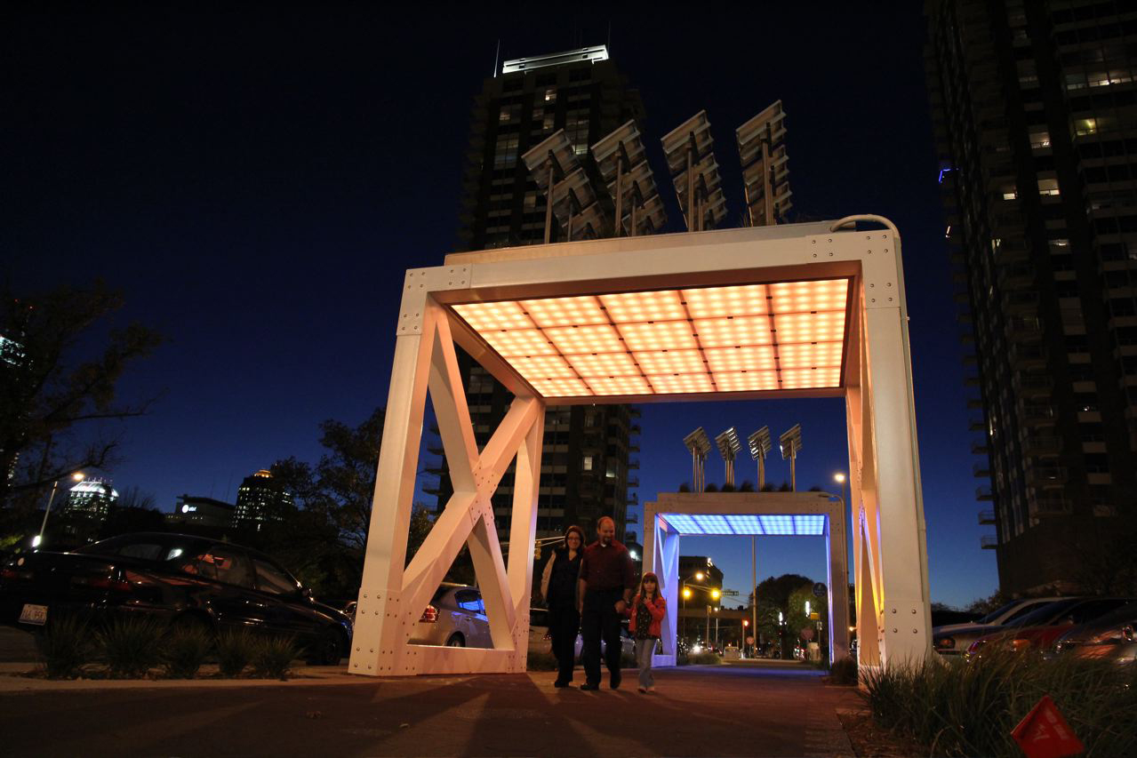 This public art installation recalls steel truss bridges and incorporates a green roof and LED lighting.