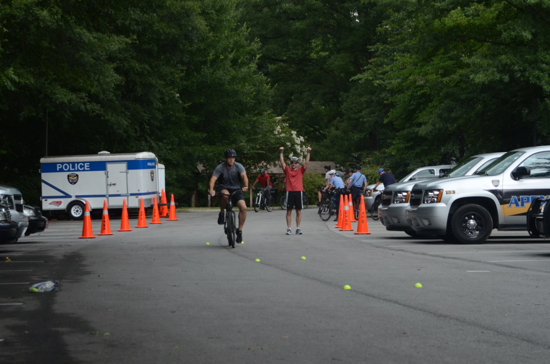 Law enforcement officers participate in hands-on exercises about bicycle safety.