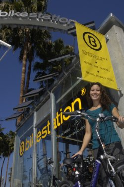 Image of a woman standing with her bike in front of the bikestation.